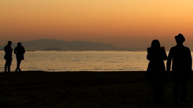 Two couples look at the sunset during the first day of spring at Shinmaiko Beach in Tatsuno, Hyogo Prefecture, Japan