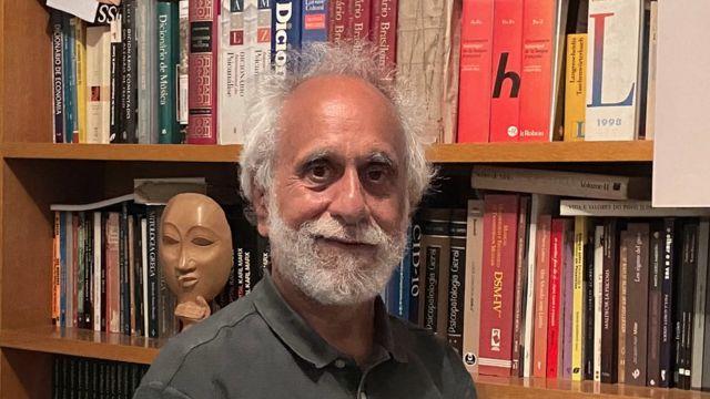 Mauro Mendes com sorriso contido em frente a estante de livros