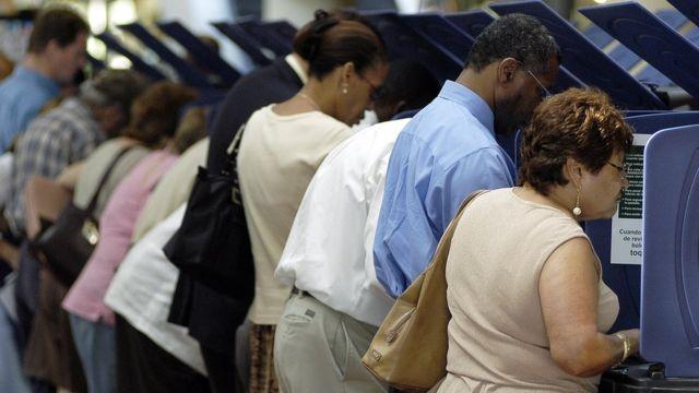 Una fila de personas votan en las elecciones.