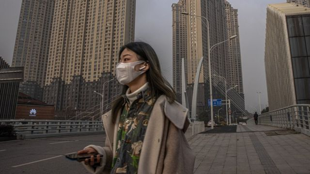 Young woman wearing a face mask, waking in Wuhan, China.