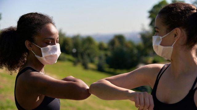 Duas jovens de máscara se cumprimentam com o cotovelo