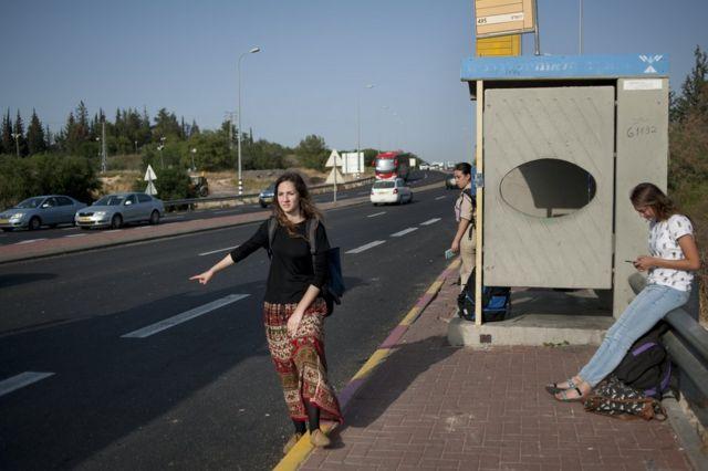 أشخاص ينتظرون في محطة حافلات