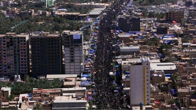 حشود من الزائرين في أحد شوارع مدينة كربلاء متوجهين لزيارة مرقد الحسين سيرا على الأقدام