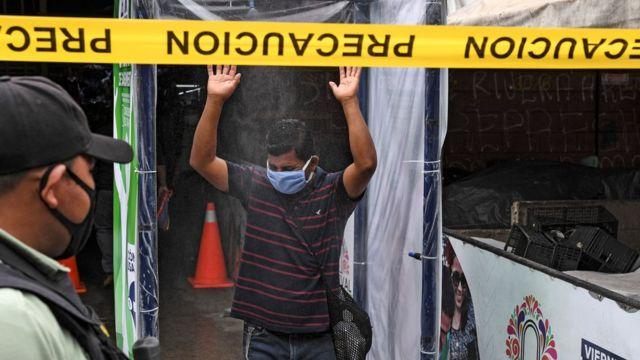 Un policía vigila gente en una cabina sanitaria de El Salvador.