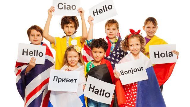 Grupo de niños con disntintas banderasy saludos en distintos idiomas.