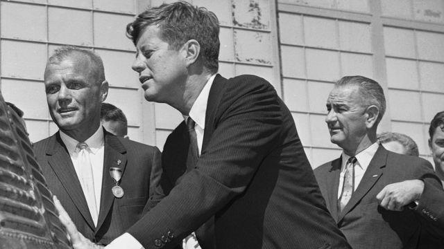 جون غلين (على اليسار) والرئيس جون كينيدي (وسط) ونائب الرئيس ليندون جونسون (على اليمين) يفحصون كبسولة الفضاء فريندشيب 7.