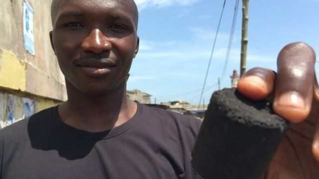 Ghana's Sampson Sayibu shows off a charcoal shape made from recycled human toilet waste