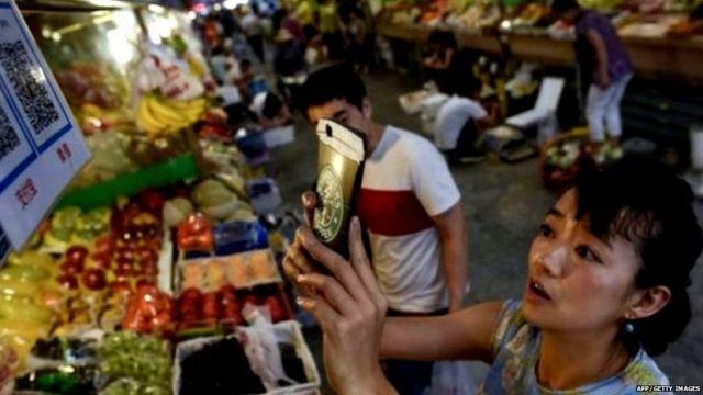 ચીનમાં ફળો ખરીદીને મોબાઈલ મારફત પેમેન્ટ કરી રહેલી મહિલા