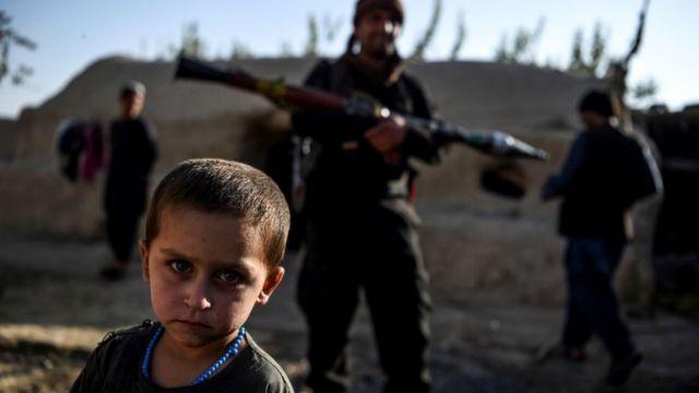 Un niño junto a policías en Afganitán