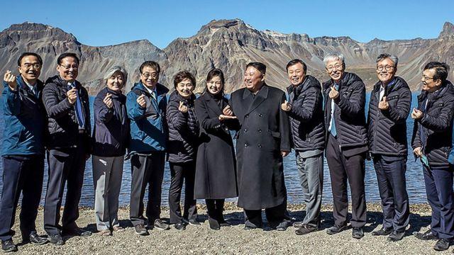 북한 김정은 국무위원장이 백두산 천지에서 남측 대표단과 기념사진을 찍고 있다