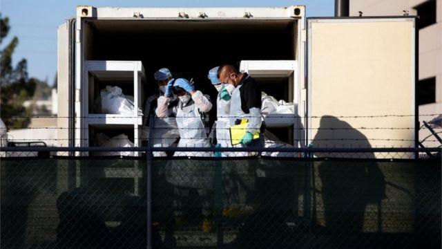 Prisioneiros ajudando a mover cadáveres
