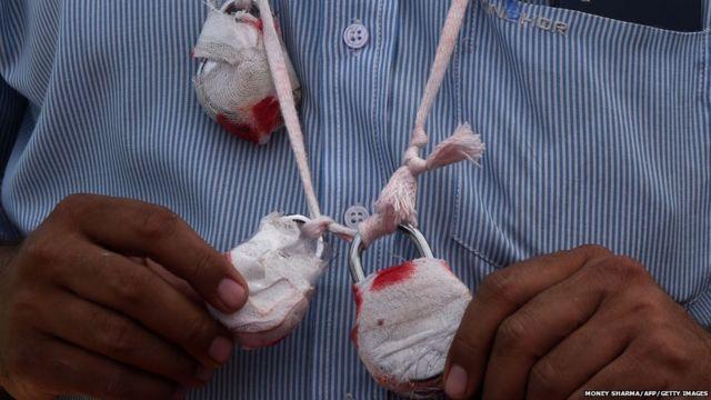 भारत की राजधानी दिल्ली में चल रहे सीलिंग अभियान के ख़िलाफ़ गले में सीलिंग युक्त तालों को लटकाकर प्रदर्शन करते एक व्यापारी