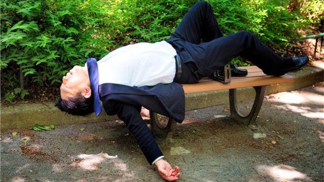 Мужчина, заснувший на скамейке в парке