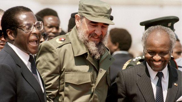 Rais wa Cuba Fidel Castro (katikati) akicheka pamoja na rais wa Zimbabwe Canaan Banana (Kulia) pamoja na waziri mkuu wa Zimbabwe Robert Mugabe (Kushoto) alipokuwa akiwasili mjini Harare, Zimbabwe - tarehe 31 Agosti 1986