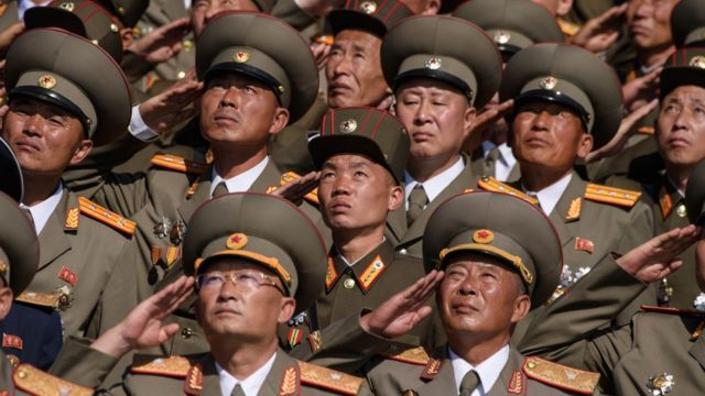 Korean People's Army (KPA) soldiers salute as they watch a mass rally
