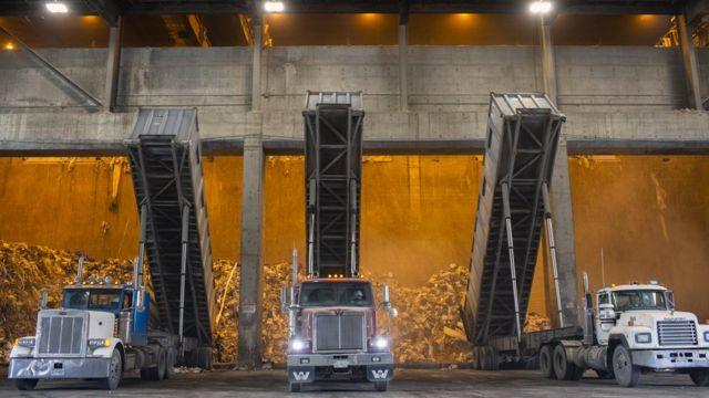 Camiones alineados frente a un horno para quemar basura en Estados Unidos.