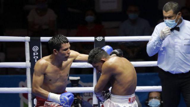 Boxeadores en el ring, el juez lleva una mascarilla