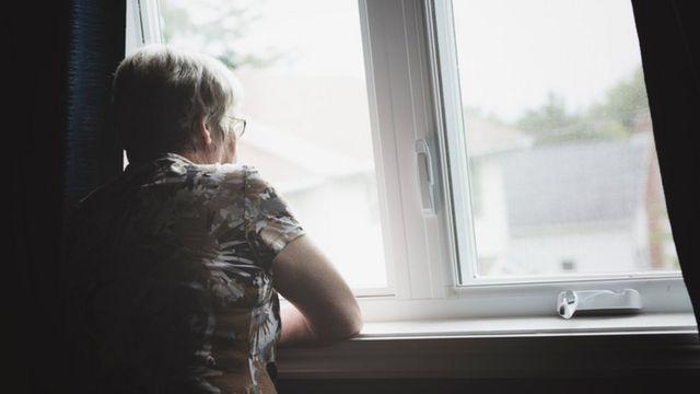 Idosa olhando pela janela