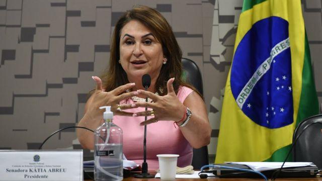 Kátia Abreu gesticula, sentada diante de mesa de comissão, com bandeira do Brasil atrás