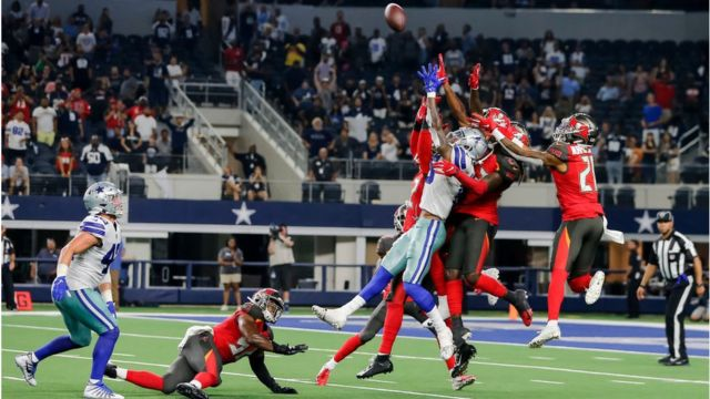 Dallas Cowboys players and Tampa Bay Buccaneers jump for a hail mary pass