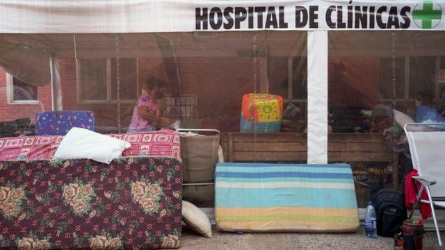 Colchões e malas em frente a fachada que diz: Hospital de Clínicas