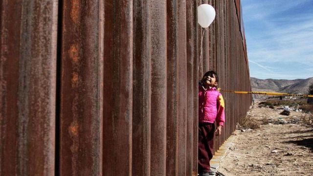 فتاة تمسك بالونا يرتفع فوقها قليلا تقف بجوار جدار حديدي ضخم