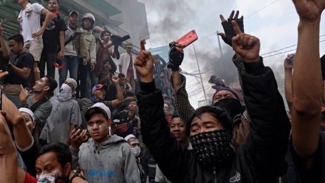ชายชาวอินโดนีเซียเยาะเย้ยตำรวจ ขณะทีการประท้วงดำเนินต่อเนื่องในกรุงจาการ์ตาเมื่อวันพุธ