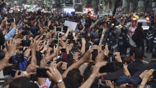 Miles de personas con sus teléfonos móviles intentan captar el cortejo fúnebre.