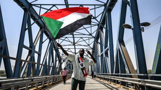 شخص يرفع علم السودان