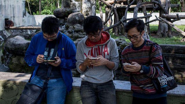 คนรุ่นใหม่กำลังดูโทรศัพท์ในมือ ในเมืองยอกยาการ์ตา อินโดนีเซีย 2016