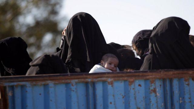Una mujer huye con un niño de la ciudad de Al-Bab que controla EI desde 2014