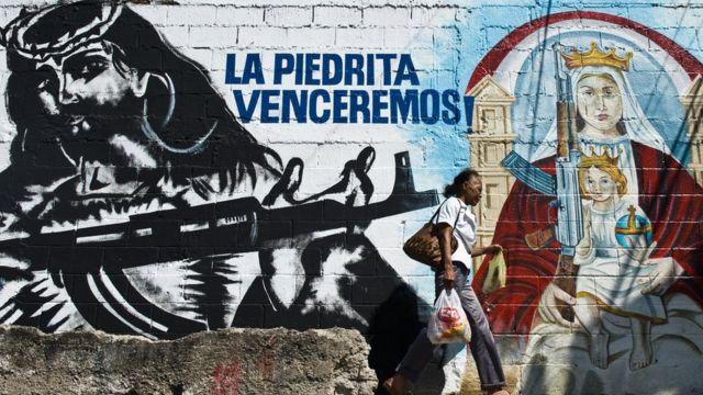 Mural en el 23 de enero que muestra un Cristo y una virgen armados.