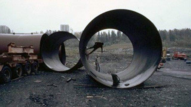 Improvised skater park with a skateboarder skating inside a ramp