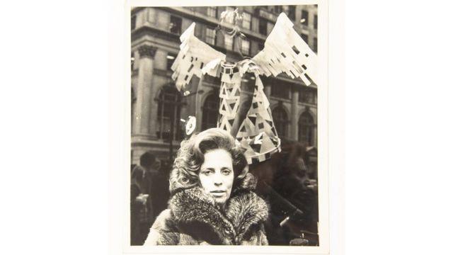 Zuzu com casaco requintado em área externa, com prédios de Nova York atrás, em foto preto e branco