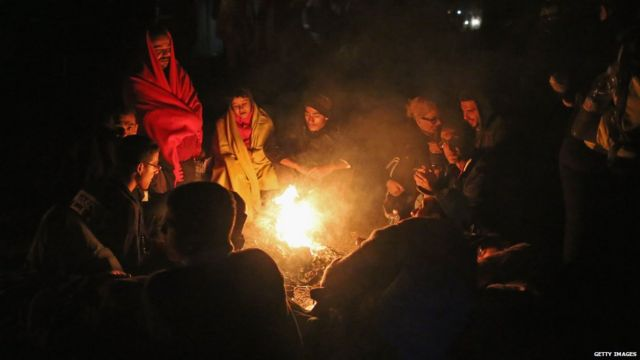 Migrants huddle round a campfire after crossing into Hungary
