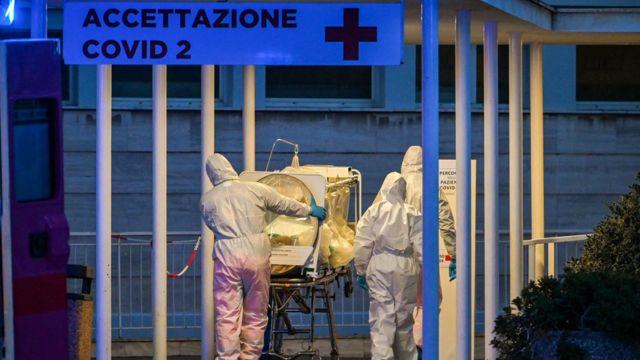 Profissionais de saúde carregam paciente em maca por corredor externo de hospital recém-construído em Roma