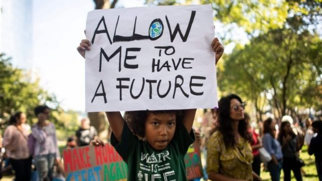 """A child holds up a sign reading, """"Allow me to have a future"""" at a climate rally in New York - one of many taking place worldwide on 20 September 2019"""