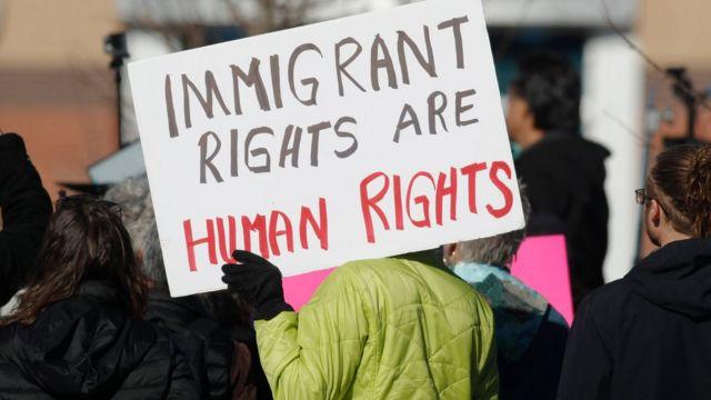 """Cartel con el texto: """"Los derechos de los inmigrantes son derechos humanos""""."""