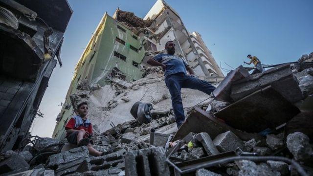 Palestinos inspecionam os escombros de sua casa destruída após ataques aéreos israelenses
