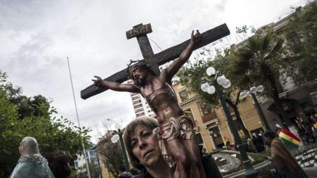 Mulher carrega um crucifixo durante protestos na Bolívia.