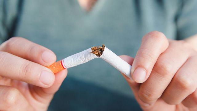 Una mujer parte un cigarrillo.