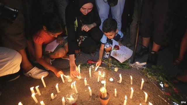 People light candles for the victims of the Tunisia killings