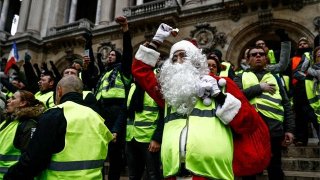 A protester dressed as Santa Claus and wearing a yellow vest (gilet jaune) demonstrates on the stairs of the Opera Garnier in Paris, on December 15, 2018