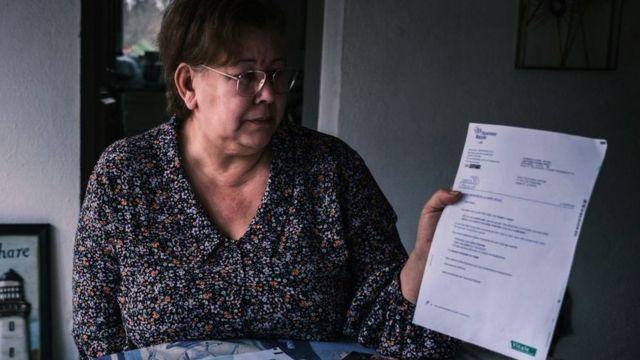 Jeanne Pouchain olha para uma carta dizendo que ela está legalmente morta