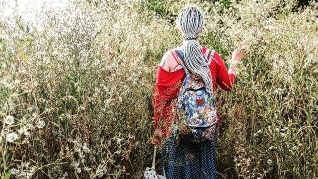 Lia caminando por un campo con flores.