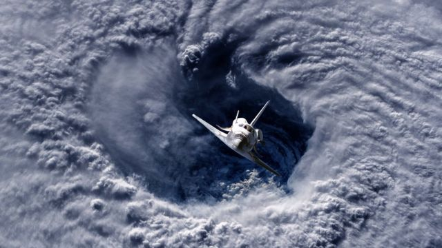 Un transbordador espacial volando sobre un huracán en la Tierra