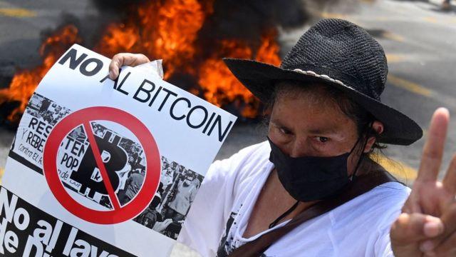 """Manifestante con un cartel de """"No al bitcoin""""."""