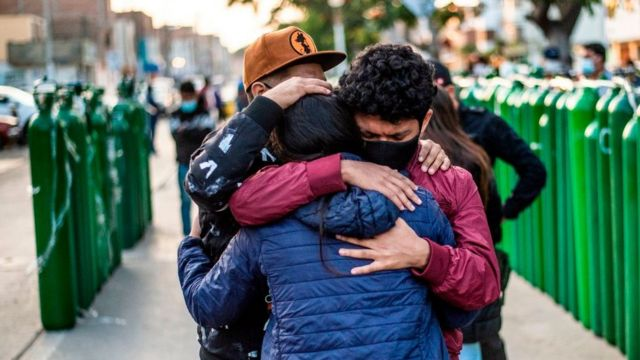 Relatives of covid patients hug each other in front of oxygen cylinders in Callao, Peru