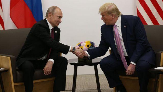 Putin akisalimiana kwa mkono na Donald Trump