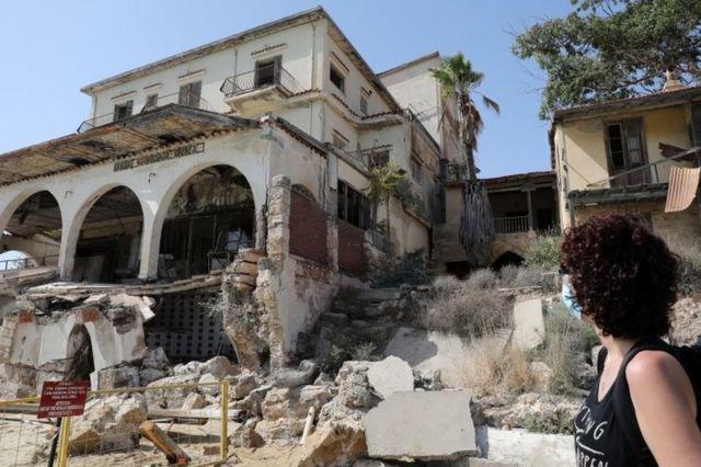 Maraş'ta harabe bir eve bakan kadın.